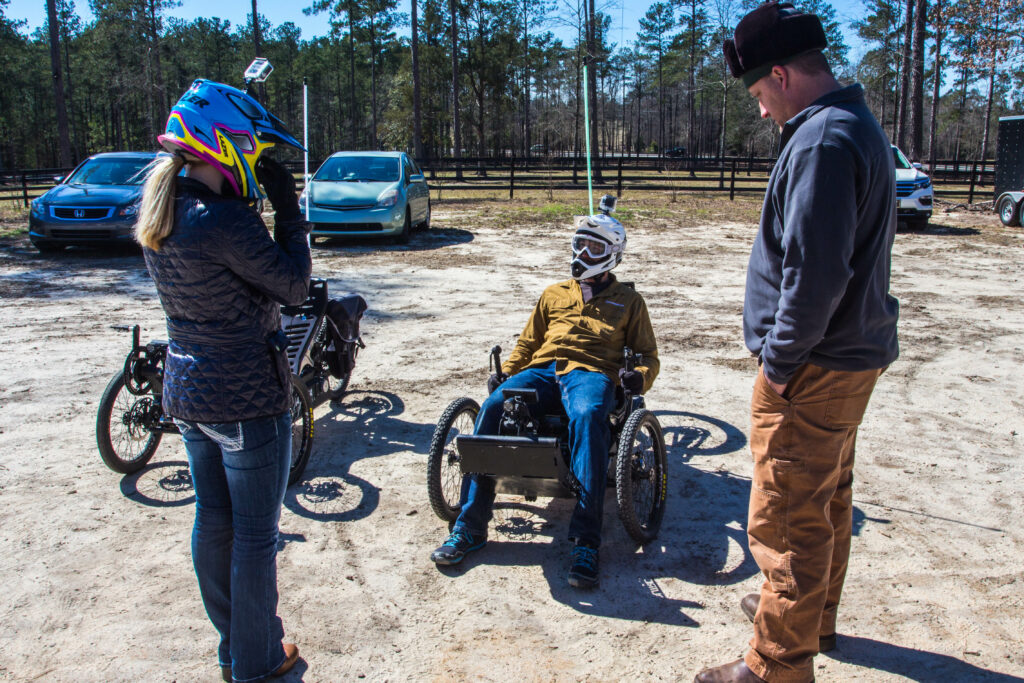 Ellerbe Kinard talks with a veteran on an Outrider USA electric adventure vehicle.