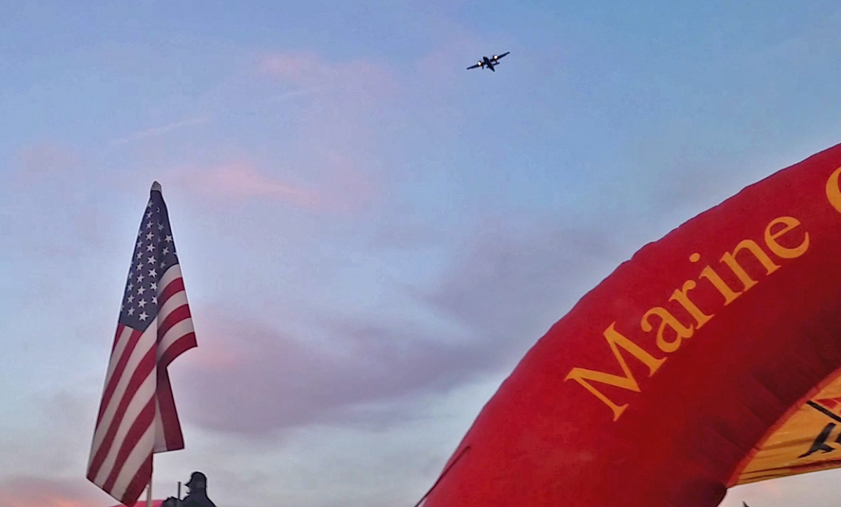 A plane passes over the Marine Corps Marathon arch